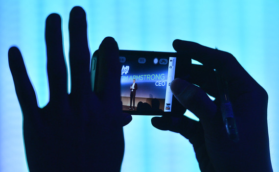 A member of the audience films Chairman and CEO of AOL, Tim Armstrong, as he speaks during the launch of the HTC One smartphone in London