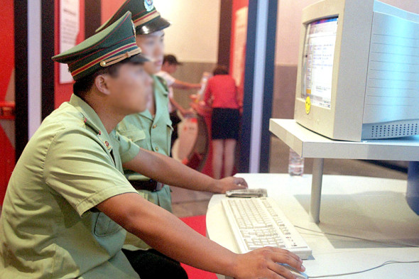 Chinese policemen surf the Internet at a computer