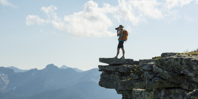 Hiker takes picture from bluff above mountains